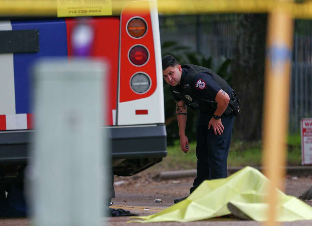 Metro police officers investigate the scene where a woman was fatally struck by a Metro bus on Peakwood Drive near Red Oak Drive Wednesday, Oct. 31, 2018, in Houston.