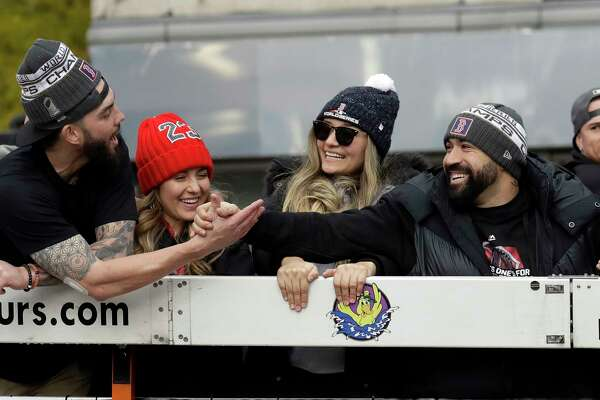 Boston Red Sox's Blake Swihart, left, shakes hands with Sandy Leon during a parade to celebrate the team's World Series championship over the Los Angeles Dodgers, Wednesday, Oct. 31, 2018, in Boston.