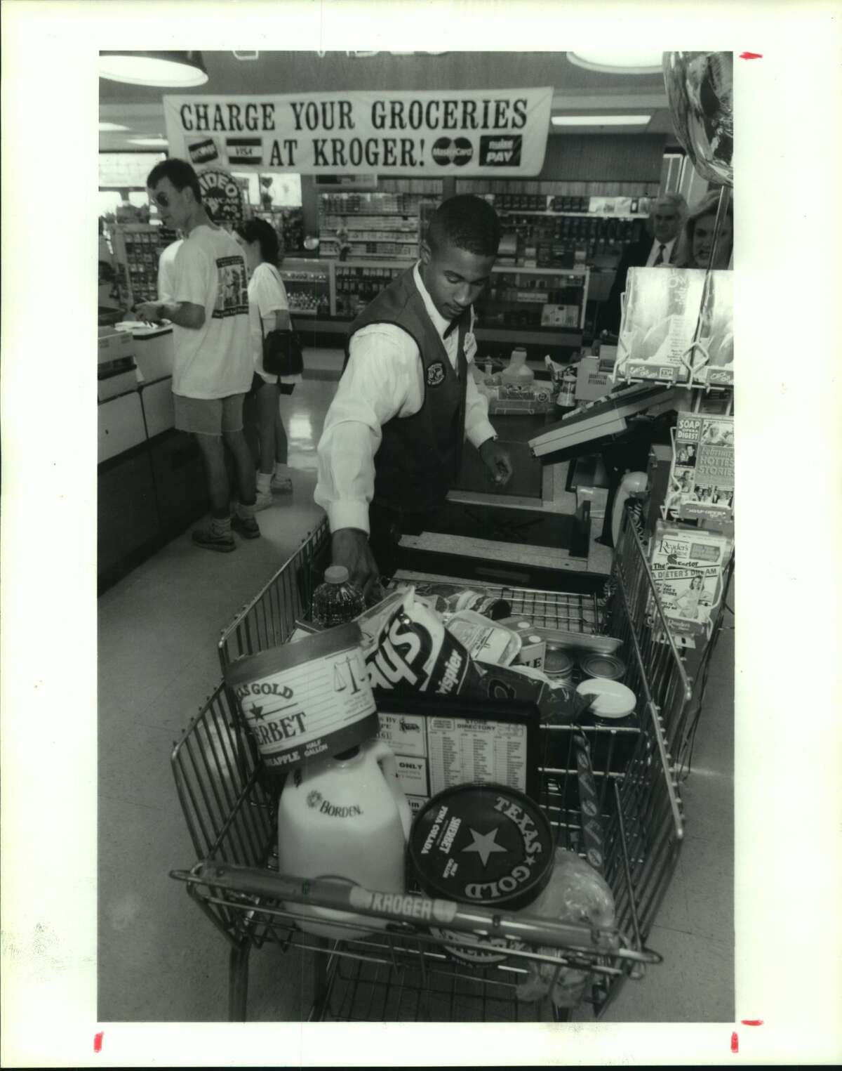 January 1993: Clayton Trim, a checker for the Kroger at 3300 Montrose, unloads a grocery cart that opens in front. The cart is designed to eliminate the extra strain of lifting items up and out.