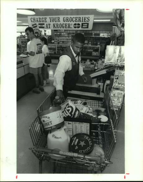 January 1993: Clayton Trim, a checker for the Kroger at 3300 Montrose, unloads a grocery cart that opens in front. The cart is designed to eliminate the extra strain of lifting items up and out. Photo: Richard Carson/Houston Chronicle
