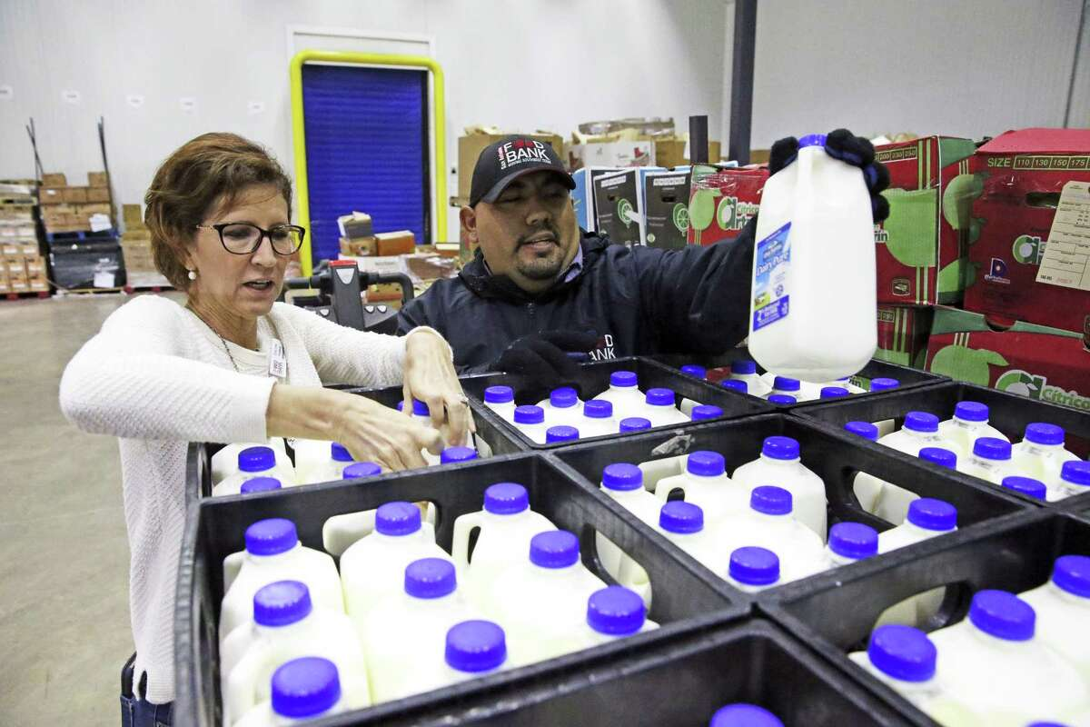 Food insecurity is one of the four social determinants of health. Here, Carey Lenss examines product with Steven Gutierrez after pallets of Oak Farms milk are unloaded at the San Antonio Food Bank on October 31.