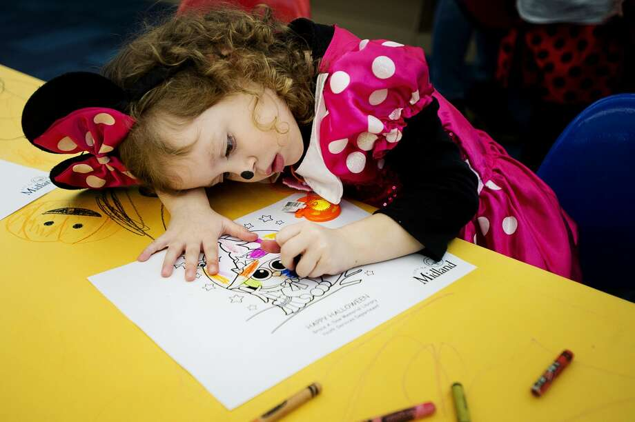 Midland resident Brinlee Fahy, 3, dressed as Minnie Mouse, colors with crayons during a Halloween celebration at the Grace A. Dow Memorial Library on Wednesday, Oct. 31, 2018. (Katy Kildee/kkildee@mdn.net) Photo: (Katy Kildee/kkildee@mdn.net)