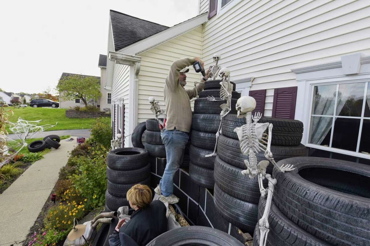 Dawn Castle, left, and her husband Paul Castle set up skeletons as part of the Halloween decorations outside their home on Wednesday, Oct. 31, 2018, in East Greenbush, N.Y. The Castles have been doing large elaborate Halloween decorations for the past 18 years. The Castles and family members had to wait until 7:45am Halloween morning to start setting up because Paul did not want the area children to see what his home would look like until after school. (Paul Buckowski/Times Union)