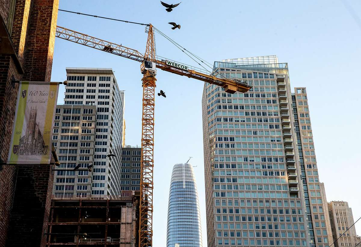 Pigeons fly past a large crane currently constructing high-density housing along Mission Street in San Francisco, Calif. Tuesday, Oct. 30, 2018.