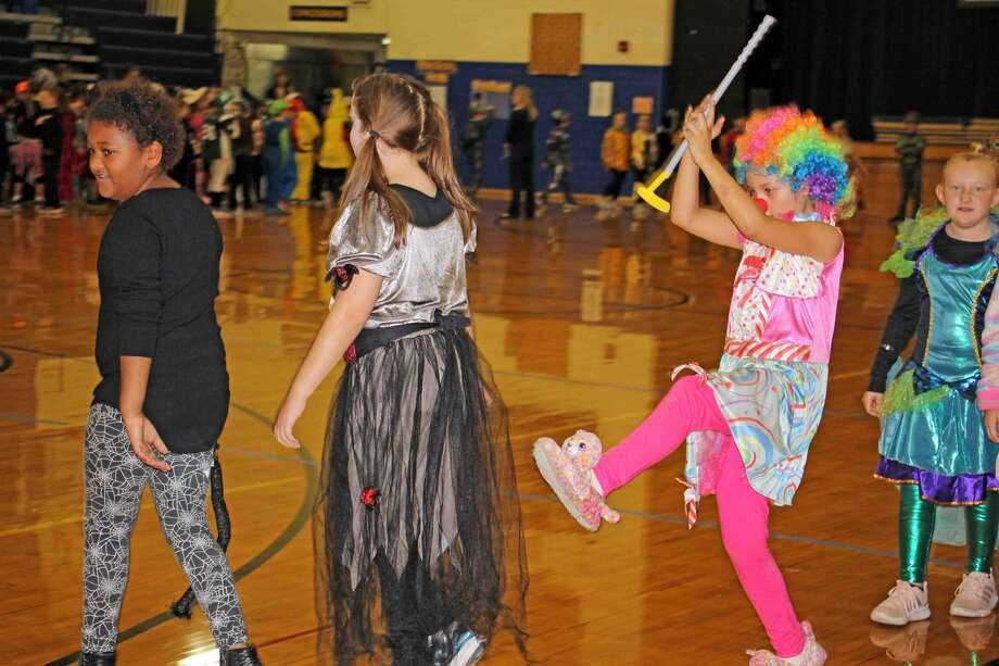 Bad Axe Middle School put on a Halloween parade and assembly Wednesday afternoon. Some of the games featured a broomstick relay race and having students compete against who can wrap up a teacher in the most toilet paper. Photo: Kate Hessling/Huron Daily Tribune