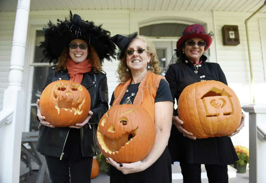 Social Work Intern Jacquie Brecher, left, and Executive Director Gaby Rattner, center, hold first-place pumpkins and Office Administrator Aixa Capozza holds a pumpkin with the CCI logo at the Halloween Pumpkin Carving Contest judging at Community Centers, Inc. of Greenwich in Greenwich, Conn. Wednesday, Oct. 31, 2018. CCI received about a dozen entries for the contest in its inaugural year and was judged by CCI staff members. In addition, Parsonage Cottage seniors painted festive Halloween apples to be displayed outside the CCI office. Photo: Tyler Sizemore / Hearst Connecticut Media / Greenwich Time