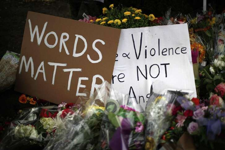 Flowers surround signs on Wednesday, Oct. 31, 2018, part of a makeshift memorial outside the Tree of Life Synagogue to the 11 people killed during worship services Saturday Oct. 27, 2018 in Pittsburgh. (AP Photo/Gene J. Puskar)