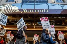 Marriott-affiliated hotel and hospitality workers strike outside of the Marriott Marquis hotel Saturday, Oct. 20, 2018 in San Francisco, Calif. before taking the streets in a massive march.
