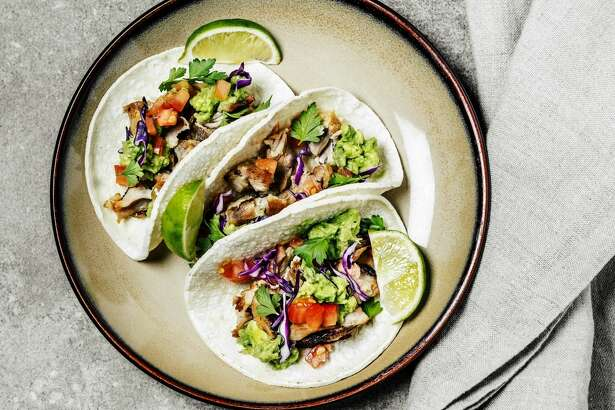 Pork tacos on a plate on gray background