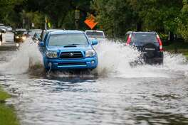 Cars pass down a flooded Willowbend Boulevard during the rain showers soaking Houston on Halloween, Wednesday, Oct. 31, 2018.