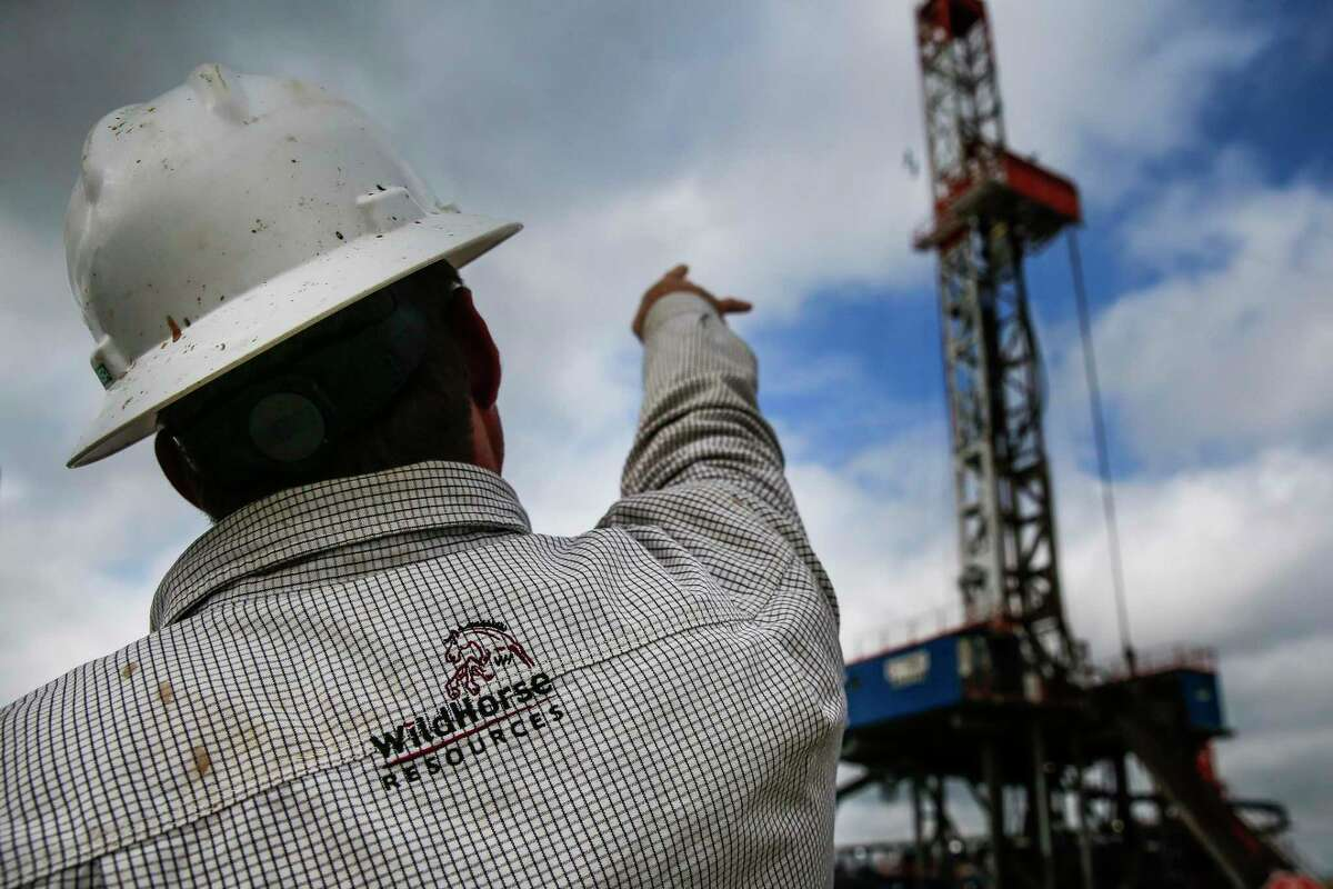WildHorse Resource Development drilling superintendent Josh Bradford points at one of the drilling rigs outside Caldwell, Texas Tuesday Oct. 2, 2018. The WildHorse oil and gas operations lie on the northeastern edge of the Eagle Ford Shale, which is seeing a modest rebound in production after the recent oil bust. (Michael Ciaglo/Houston Chronicle via AP)