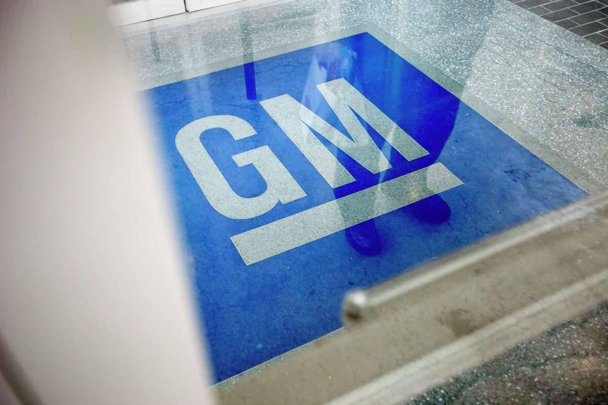 FILE - In this Jan. 10, 2013, file photo, the logo for General Motors decorates the entrance at the site of a GM information technology center in Roswell, Ga. General Motors is trying to cut costs by offering buyouts to about 18,000 white-collar workers in North America. The company made the offer Wednesday, Oct. 31, 2018, to salaried workers with 12 or more years of service. (AP Photo/David Goldman, File)