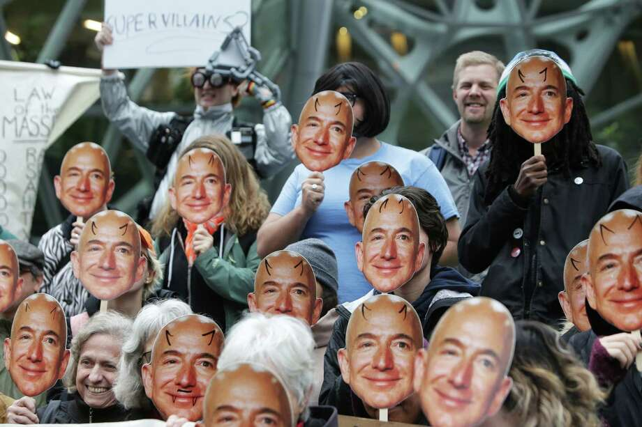 "Several dozen protesters hold up Jeff Bezos masks as they gather downtown to denounce Amazon for providing their facial recognition software, ""Rekognition,"" to the Immigration and Customs Enforcement Agency (ICE) and, thereby, supporting the Trump Administration immigration policies, Wednesday, Oct. 31, 2018. The event was organized by NWDC Resistance and Mijente. Photo: GENNA MARTIN, SEATTLEPI.COM / SEATTLEPI.COM"