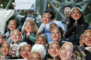"""Several dozen protesters hold up Jeff Bezos masks as they gather downtown to denounce Amazon for providing their facial recognition software, """"Rekognition,"""" to the Immigration and Customs Enforcement Agency (ICE) and, thereby, supporting the Trump Administration immigration policies, Wednesday, Oct. 31, 2018. The event was organized by NWDC Resistance and Mijente."""