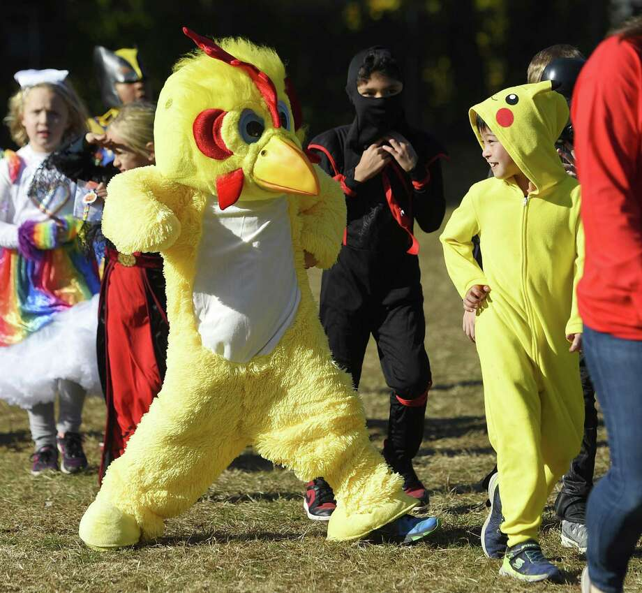 "Second-grader Rhys Maloney, left, pretends to get in a ""chicken fight"" with classmate Hiroto Kobayashi, dressed as Pikachu, at the annual Halloween parade at Cos Cob School in the Cos Cob section of Greenwich, Conn. Wednesday, Oct. 31, 2018. The school bussed in kindergarten through second graders displaced from the school's water damage to participate in the parade as teachers and staff jokingly sported lifeguard costumes. Photo: Tyler Sizemore / Hearst Connecticut Media / Greenwich Time"