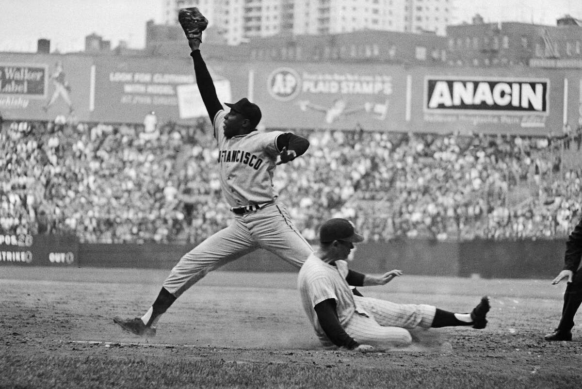 Caption: Bobby Richardson slides safely into first as Willie McCovey stretches for the late throw during game 5 of the 1962 World Series between the San Francisco Giants and New York Yankees. The Yankees defeated the Giants 4 games to 3.