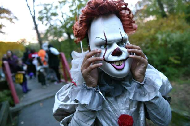 Niyel Cornelius, 12, of New Haven dressed as the clown, It, adjusts her mask before the start of the Trunk or Treat event at Edgewood Park in New Haven on October 31, 2018.