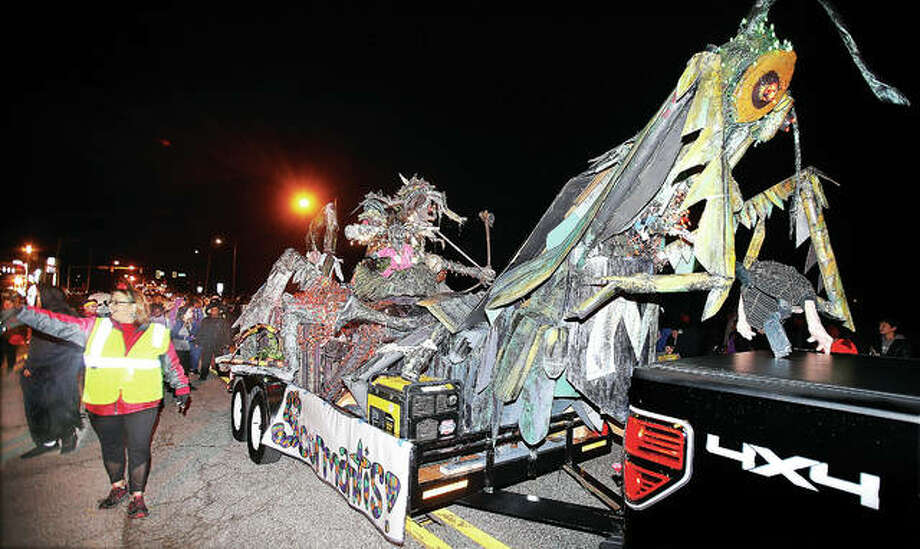 """The Alton Middle School art classes beast """"The Scormantis,"""" half scorpion and half praying mantis, moves through the 102nd annual Alton Halloween Parade Wednesday night. Thanks to the rain mostly staying to the south, thousands turned out again this year and lined the parade route to watch the floats and marching bands move through the downtown Alton area. More photos at thetelegraph.com. Photo: John Badman 