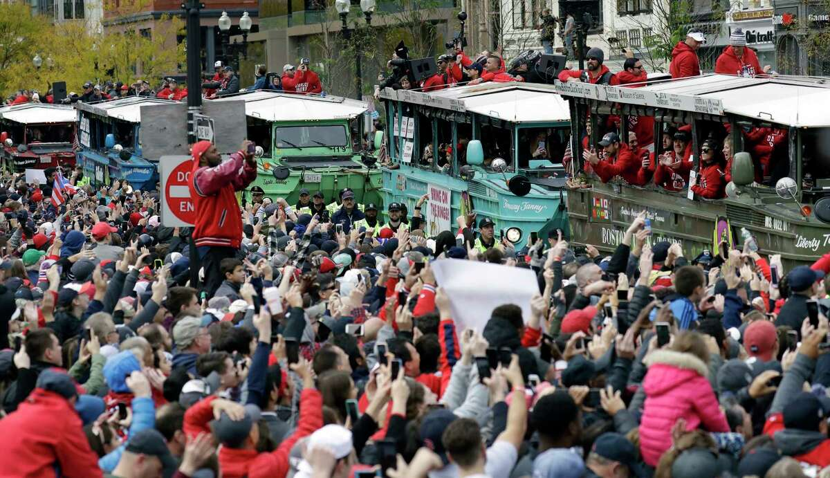 Fans cheer the Boston Red Sox passing by in duckboats during a parade to celebrate the team's World Series championship over the Los Angeles Dodgers, Wednesday, Oct. 31, 2018, in Boston. (AP Photo/Elise Amendola)