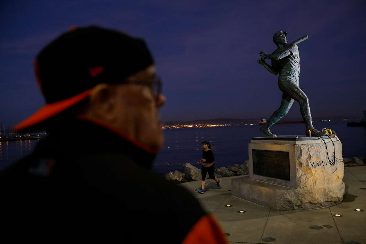 Lester Verrett (L) visits the Willie McCovey statue near AT&T park hours after the news of his death was announced in San Francisco, California, on Wednesday, Oct. 31, 2018.