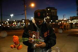 Giants fan Erik Wassmer prepares to bring flowers to Willie McCovey's statue hours after the news of his death was announced in San Francisco, California, on Wednesday, Oct. 31, 2018.