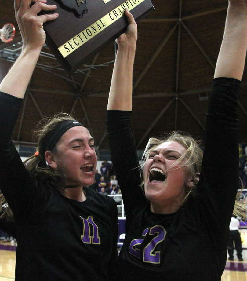 Routt's Annika Black (left) and Addie Huey sing the school song as they celebrate the Rockets' sectional championship victory Wednesday night. Routt beat Mount Pulaski in two games to advance to super-sectionals Friday night. Photo: Dennis Mathes | Journal-Courier