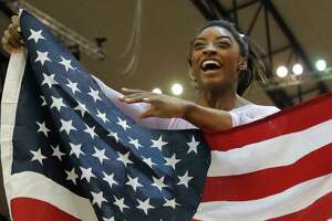 Gold medallist and four-times All-Around world champion Simone Biles of the U.S. celebrates with the national flag after the Women's All-Around Final of the Gymnastics World Chamionships at the Aspire Dome in Doha, Qatar, Thursday, Nov. 1, 2018. (AP Photo/Vadim Ghirda)