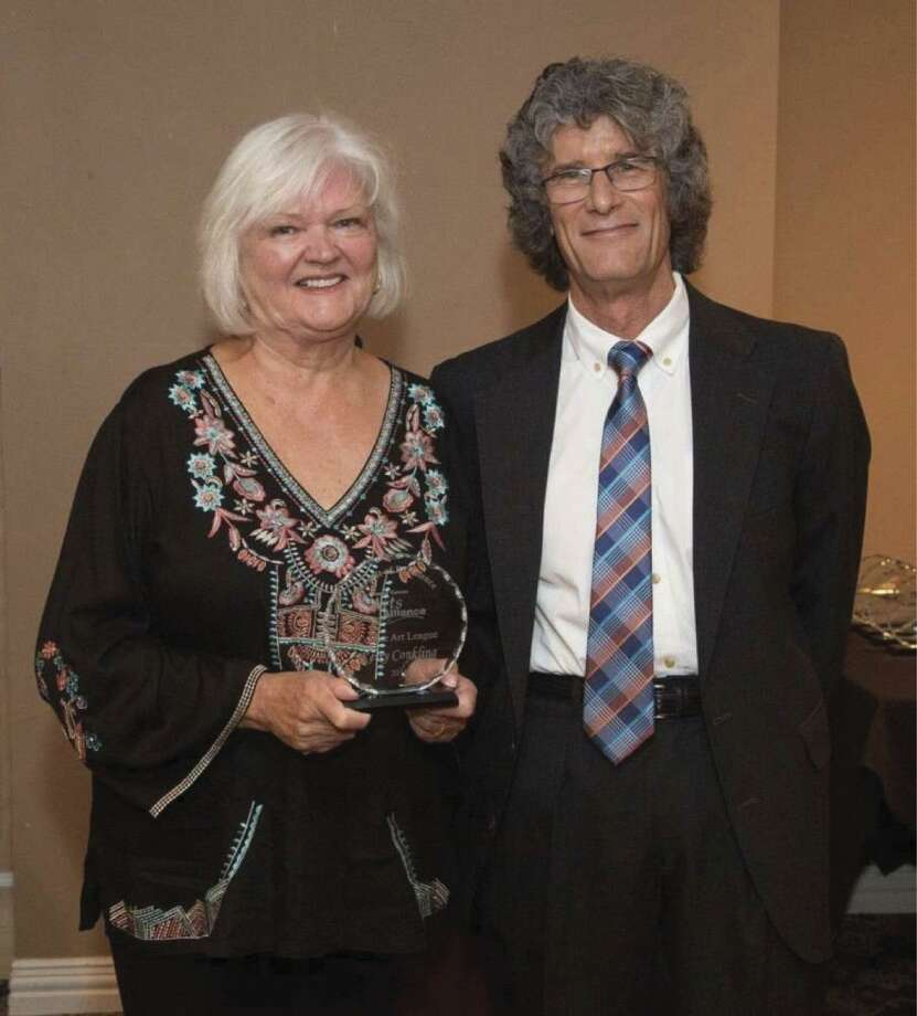 Kerry Conkling holding the Greater Conroe Arts Alliance's 2018 Pursuit of Excellence Award for the visual arts, which was presented to her on Oct. 25. Current Conroe Art League President Brett Hall is standing next to Kerry.