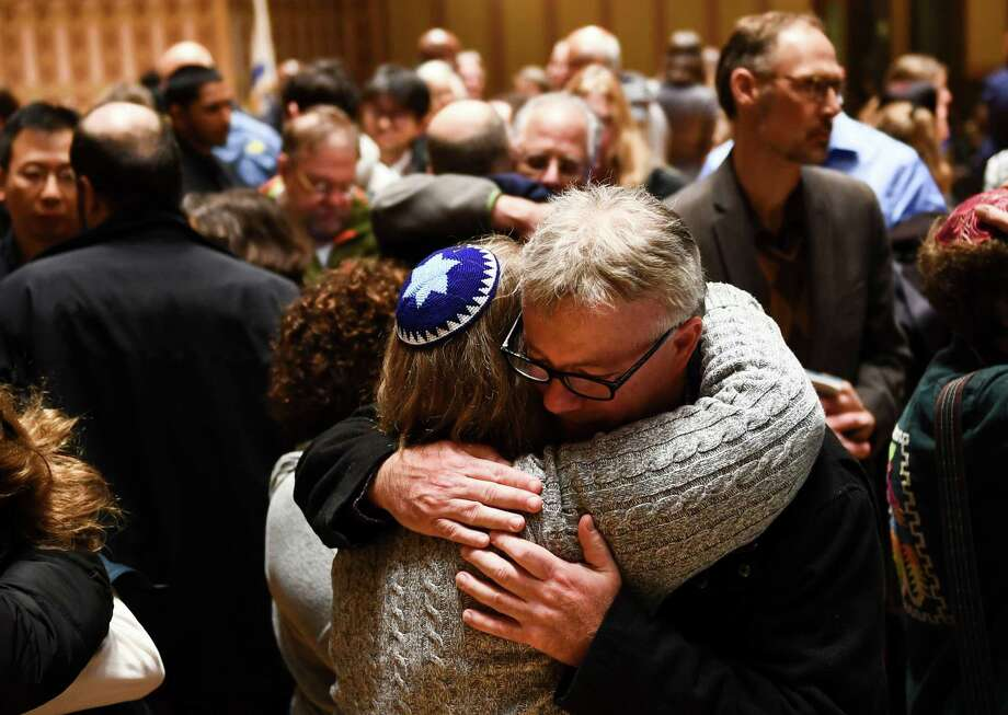 "People hug after a vigil, to remember the victims of the shooting at the Tree of Life synagogue the day before, at the Allegheny County Soldiers Memorial on October 28, 2018, in Pittsburgh, Pennsylvania. - A man suspected of bursting into a Pittsburgh synagogue during a baby-naming ceremony and gunning down 11 people has been charged with murder, in the deadliest anti-Semitic attack in recent US history. The suspect -- identified as a 46-year-old Robert Bowers -- reportedly yelled ""All Jews must die"" as he sprayed bullets into the Tree of Life synagogue during Sabbath services on Saturday before exchanging fire with police, in an attack that also wounded six people. (Photo by Brendan Smialowski / AFP)BRENDAN SMIALOWSKI/AFP/Getty Images Photo: BRENDAN SMIALOWSKI, Contributor / AFP/Getty Images / AFP or licensors"