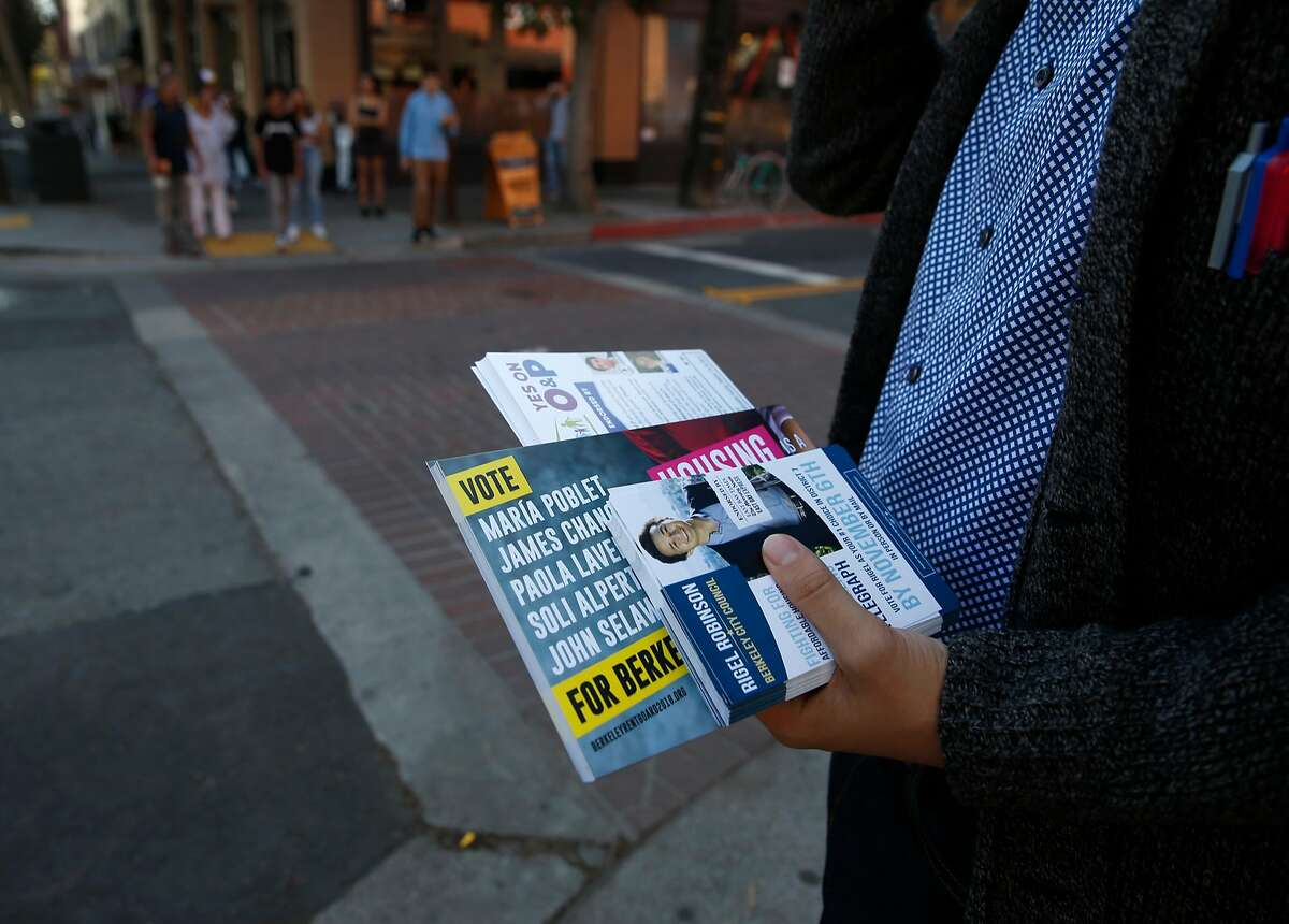 Rigel Robinson, a candidate running for the Berkeley City Council District 7 seat, carries voter information while walking on Telegraph Avenue in Berkeley, Calif. on Saturday, Oct. 27, 2018.