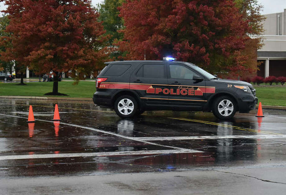 An Edwardsville Police Department vehicle sits in front of the entrance of Edwardsville High School Thursday morning after an evacuation of all students and staff. Photo: Matt Kamp | Intelligencer