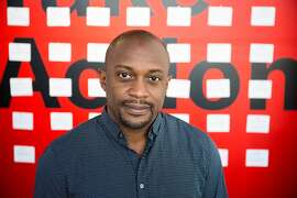 "Hank Willis Thomas, 42, a Guggenheim-winning conceptual artist and California College of the Arts (CCA) alum, co-founded For Freedoms, a national platform for creative civic engagement. He stands in front of the entrance to ""Take Action/ A For Freedoms Exhibition,"" at CCA Hubbell Street galleries in San Francisco. CCA is a co-sponsor of For Freedoms. In concert with the 2018 midterm elections, there are multiple For Freedoms exhibits in the Bay Area, including at the Oakland Museum of Art and the Cantor Arts Center at Stanford University."