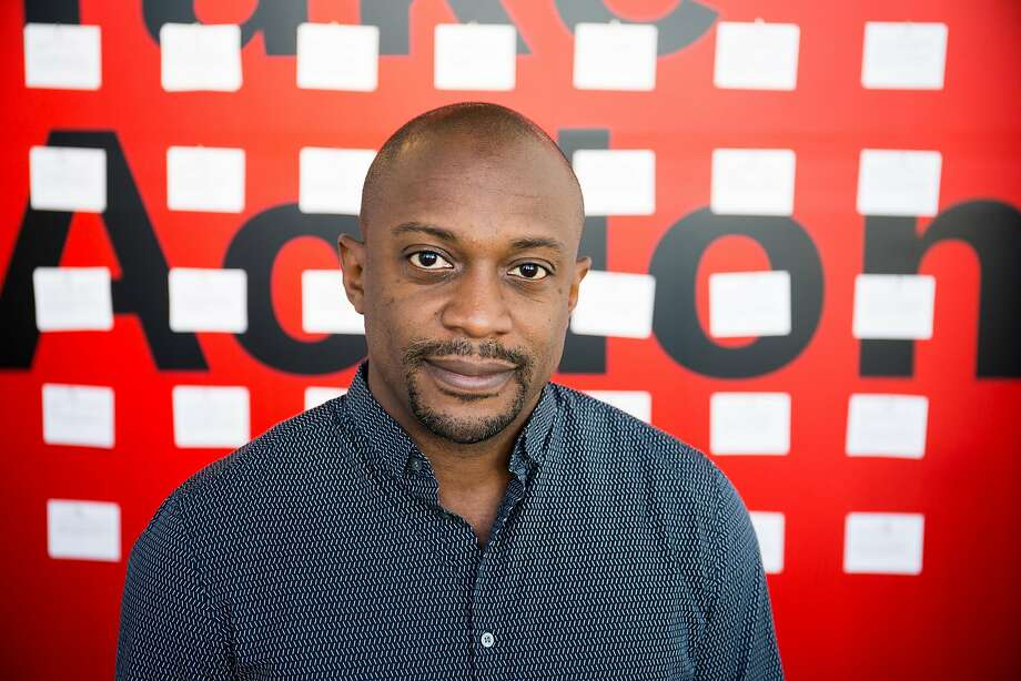 """Hank Willis Thomas, 42, a Guggenheim-winning conceptual artist and California College of the Arts (CCA) alum, co-founded For Freedoms, a national platform for creative civic engagement. He stands in front of the entrance to """"Take Action/ A For Freedoms Exhibition,"""" at CCA Hubbell Street galleries in San Francisco. CCA is a co-sponsor of For Freedoms. In concert with the 2018 midterm elections, there are multiple For Freedoms exhibits in the Bay Area, including at the Oakland Museum of Art and the Cantor Arts Center at Stanford University. Photo: Photo By Maggie Beasley / Courtesy Of CCA"""