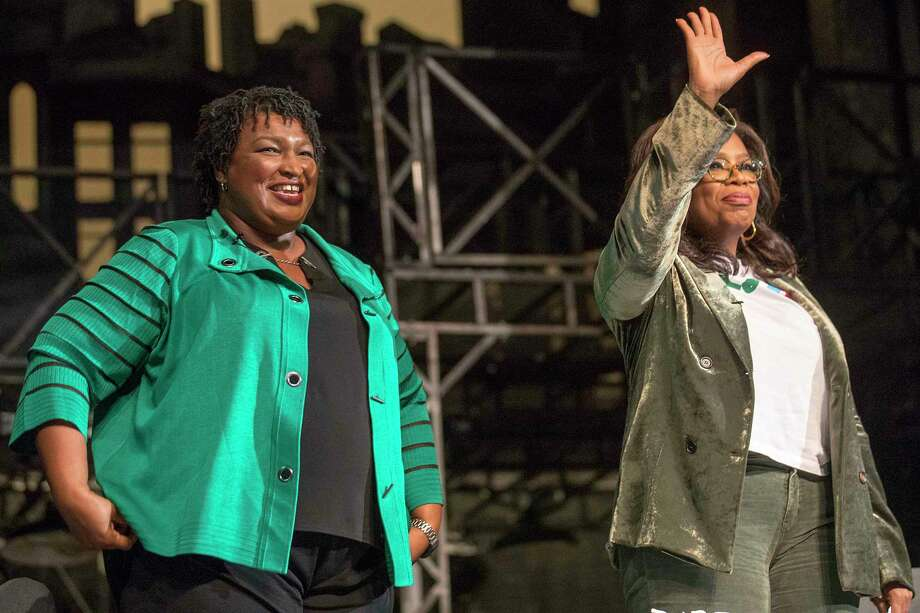 Oprah Winfrey and Georgia gubernatorial candidate Stacey Abrams wave goodbye to a crowd gathered for a town hall conversation at the Cobb Civic Center's Jennie T. Anderson Theatre in Marietta, Ga., Thursday, Nov. 1, 2018. Winfrey visited Georgia on Thursday to canvass neighborhoods in Metro Atlanta and show her support for gubernatorial candidate Stacey Abrams. (Alyssa Pointer /Atlanta Journal-Constitution via AP) Photo: Alyssa Pointer, AP / Atlanta Journal-Constitution