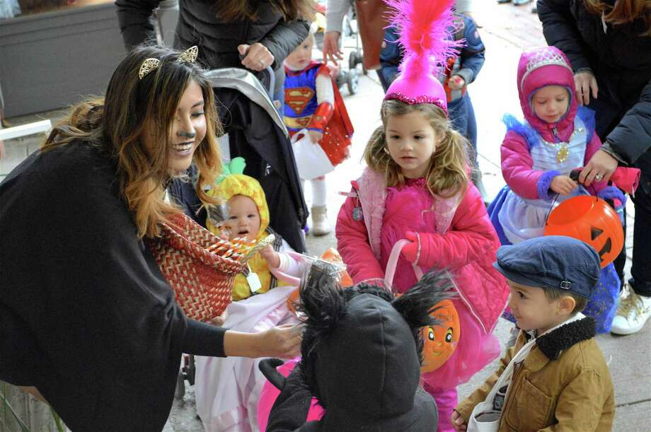 Diana Herrera of Browne & Co. was among the merchants generously giving out treats at the Darien Community Association's annual Halloween parade on Oct. 26 in Darien. Photo: Jarret Liotta / For Hearst Connecticut Media / Darien News Freelance