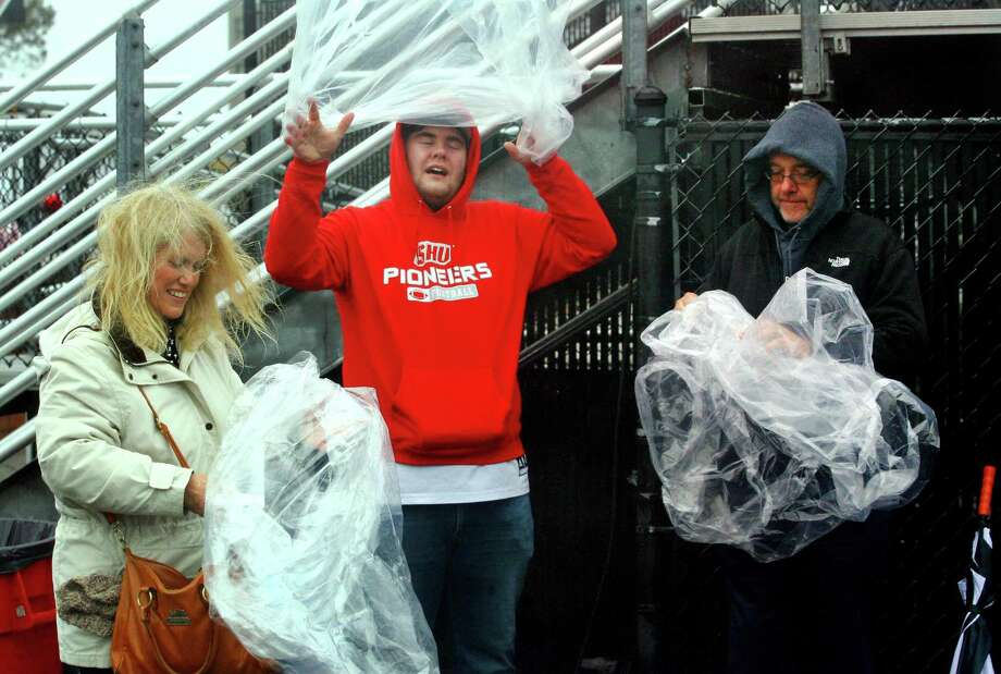 Student Brad Wasserman, center, and his parents Lori and Mike struggle to don ponchos as it rains during college football action between Sacred Heart and Bryant in Fairfield on Saturday. Photo: Christian Abraham / Hearst Connecticut Media / Connecticut Post