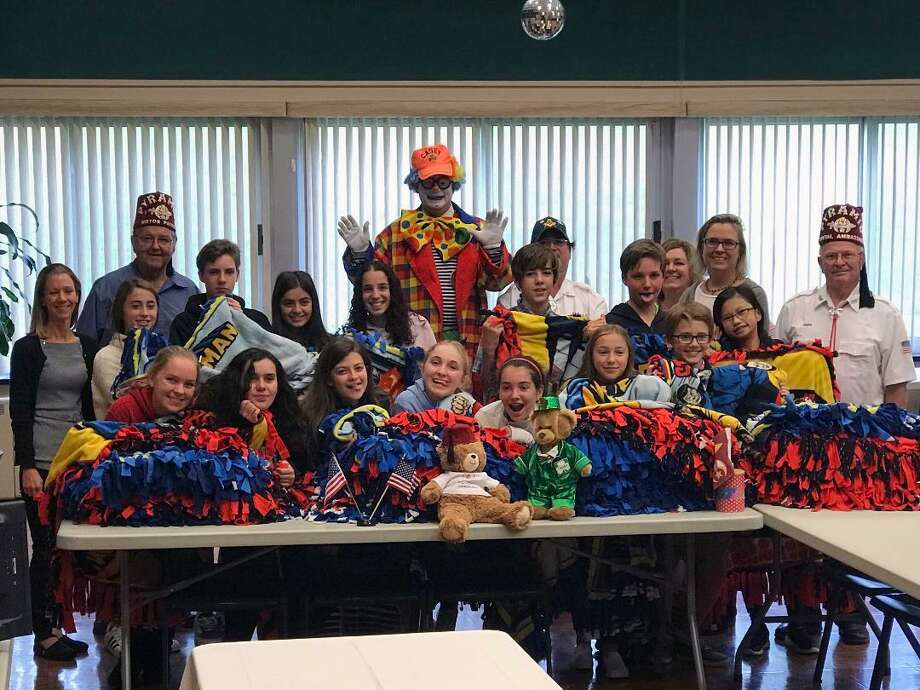 Students from religious education classes at St. Luke's Church in Westport, Connecticut, recently conducted a community service project. Students met with members of the Pyramid Shrine Temple Motor Patrol and Clown Units. Students made decorative blankets which will be given to needy children receiving medical care at the Shriner's Hospital. In addition, students participated in a multi-media educational program with the Pyramid Shriners to learn more about services provided at the Shriner's Hospital for Children. Photo: Contributed Photo