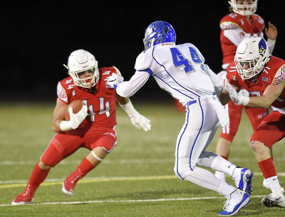 Greenwich's Jack Warren (44) carries the ball looking to get around Fairfield Ludlowe's Jake Northrop on Oct. 24. Photo: Matthew Brown / Hearst Connecticut Media / Stamford Advocate