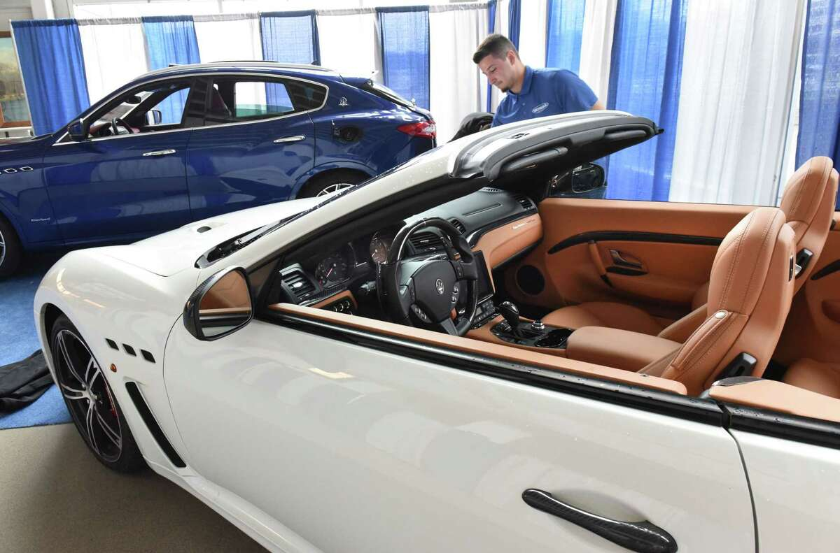 Jake Rivera cleaning up a Maserati Levante, left, and a Maserati GranTurismo convertible during set up for the Albany Auto Show at the Times Union Center on Thursday, Nov. 1, 2018 in Albany, N.Y. (Lori Van Buren/Times Union)