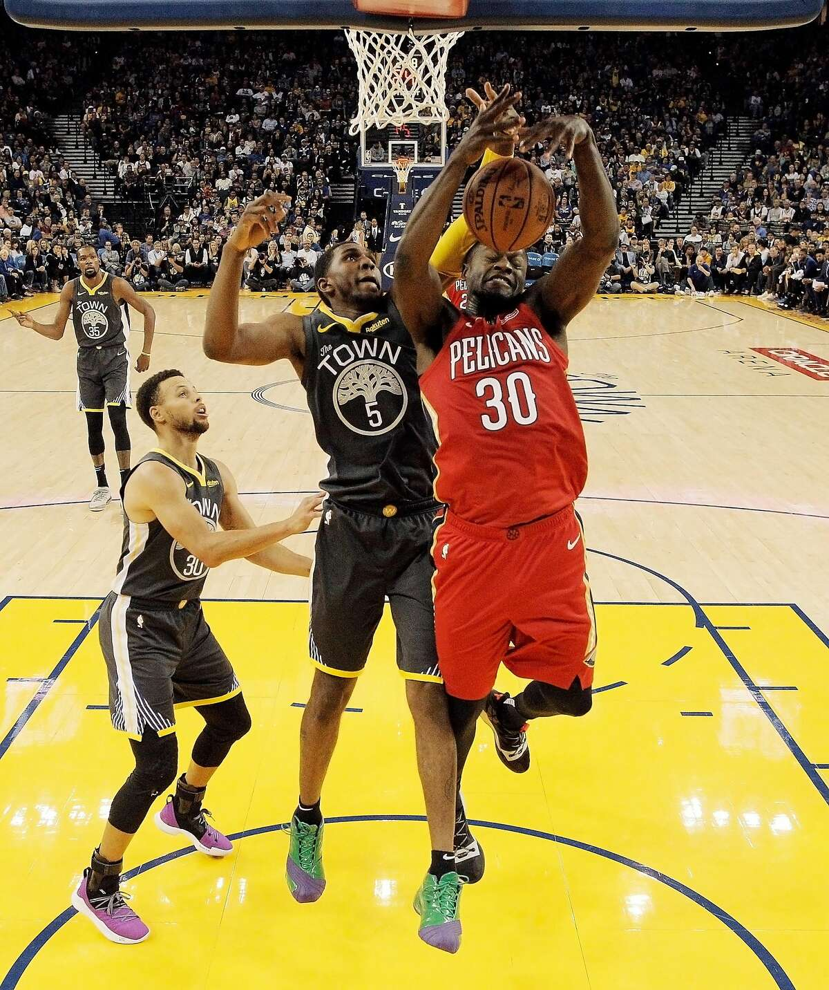 Kevon Looney (5) defends against a shot by Julius Randle (30) in the first half as the Golden State Warriors played the New Orleans Pelicans at Oracle Arena in Oakland, Calif., on Wednesday, October 31, 2018.