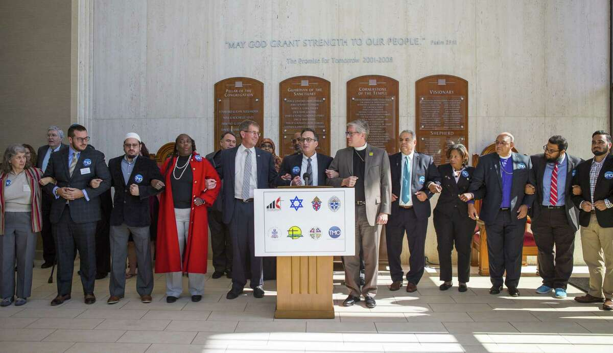 Faith leaders lock arms with Rabbi David Lyon (center) during a press conference by interfaith leaders from around the Houston region organized by The Metropolitan Organization, Thursday, Nov. 1, 2018, at Congregation Beth Israel in Houston.