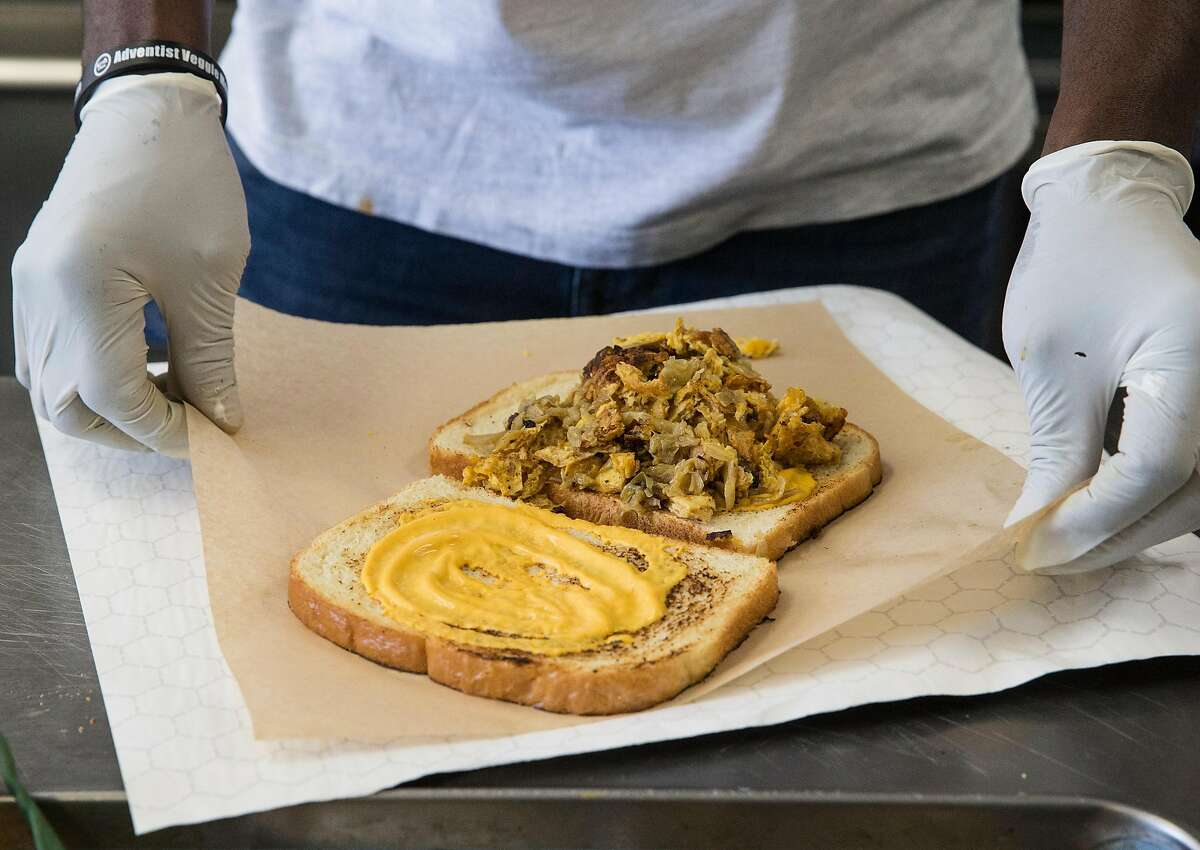 Chef GW Chew prepares a plant-based chicken melt sandwich behind the counter of The Veg Hub in Oakland, Calif. Wednesday, Oct. 31, 2018.