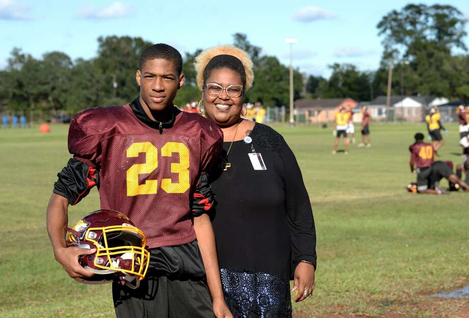 Anthony Berry stands with Bennie Berry his adopted mother and former teacher during football practice at Beaumont United High School on Thursday. Berry.   
