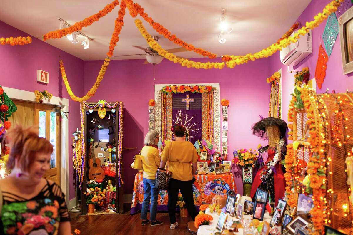 """Visitors look at the remembrance altars of local community members honoring members of their families who have passed away at the Esperanza Peace & Justice Center's annual Dia de los Muertos Celebration on November 1, 2018. """"It's about community,"""" Graciela Sanchez, executive director of Esperanza said, """"and getting them to think about it."""" Sanchez grew up in the neighborhood, and says that it's important for members of the community to feel involved in this celebration that's been going on for 41 years in the San Antonio neighborhood. It was originally started by the Centro Cultural Aztlan, but has been carried forward by Esperanza and other groups."""