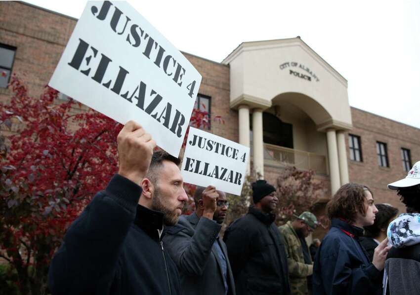 Eli Berkowitz, left, and Cedric Fulton hold up signs during a rally for Ellazar Williams Thursday, Nov. 1, 2018 at the Albany Police Department Headquarters. (Phoebe Sheehan/Special to the Times Union)