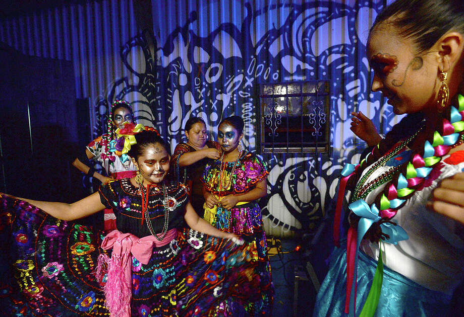 Southeast Texas Ballet Folklorico director Micaela Moreno (right) looks on as Jocelynne Martinez and fellow dancers await the start of their performance at the annual Dia De Los Muertos celebration at Tacos La Bamba, Thursday. Live music, $1 tacos and costumes were among the highlights of the event. Photo taken Thursday, November 1, 2018 Kim Brent/The Enterprise Photo: Kim Brent/The Enterprise