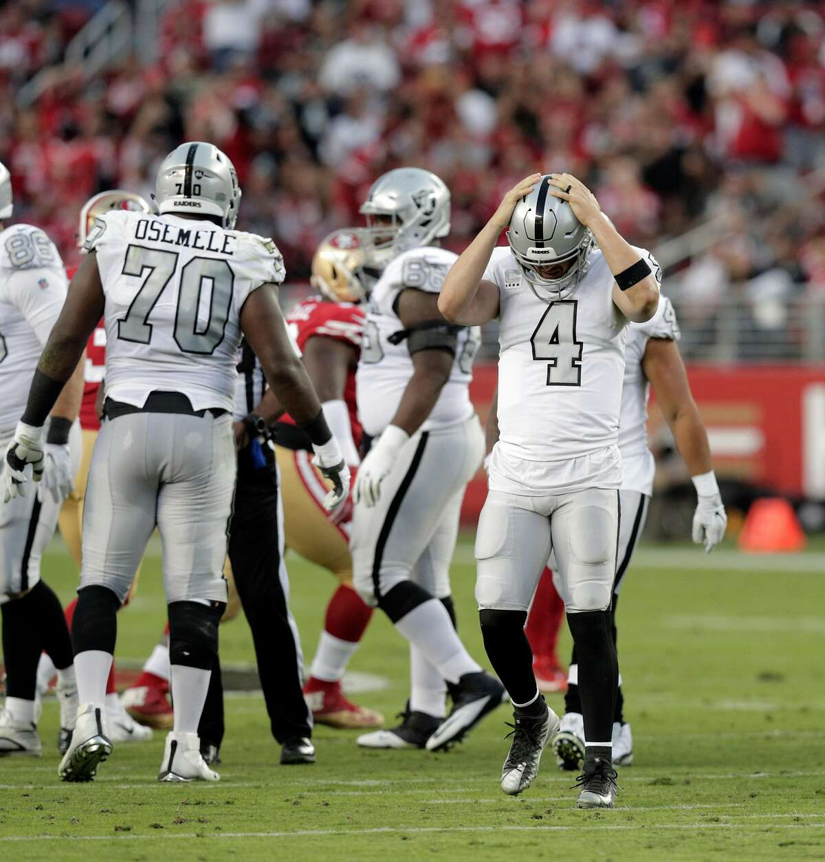 Derek Carr (4) holds his head after being sacked in the second quarter as the San Francisco 49ers played the Oakland Raiders at Levi's Stadium in Santa Clara, Calif., on Thursday, November 1, 2018.