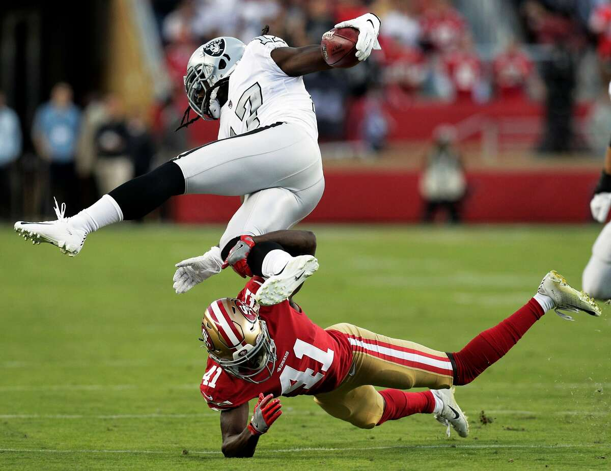 Raiders's Dwayne Harris (17) leaps over Emmanuel Moseley (41) on a kickoff return in the first quarter as the San Francisco 49ers played the Oakland Raiders at Levi's Stadium in Santa Clara, Calif., on Thursday, November 1, 2018.