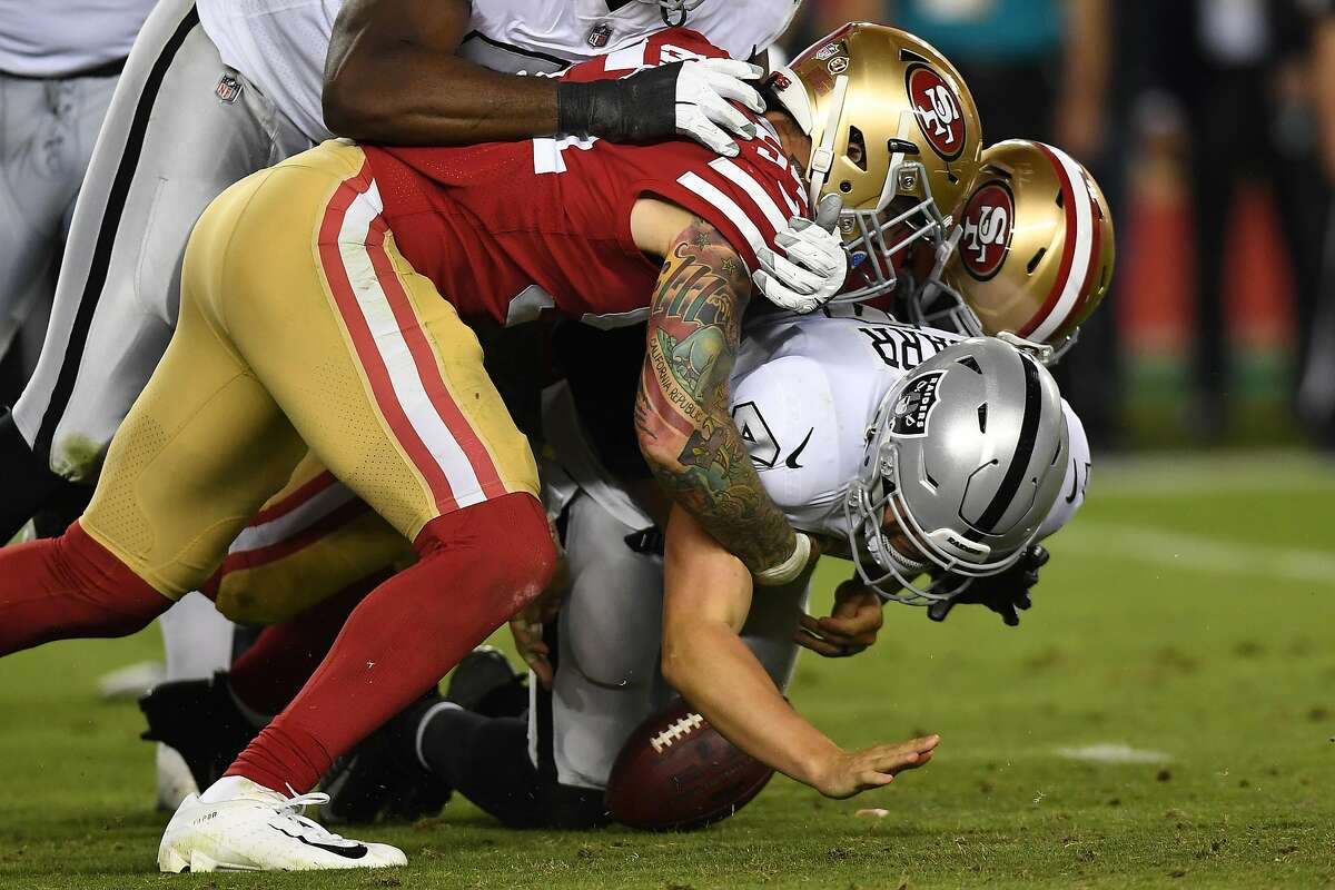 Derek Carr #4 of the Oakland Raiders is sacked by Cassius Marsh #54 and Dekoda Watson #97 of the San Francisco 49ers and loses the ball during their NFL game at Levi's Stadium on November 1, 2018 in Santa Clara, California. (Photo by Thearon W. Henderson/Getty Images)