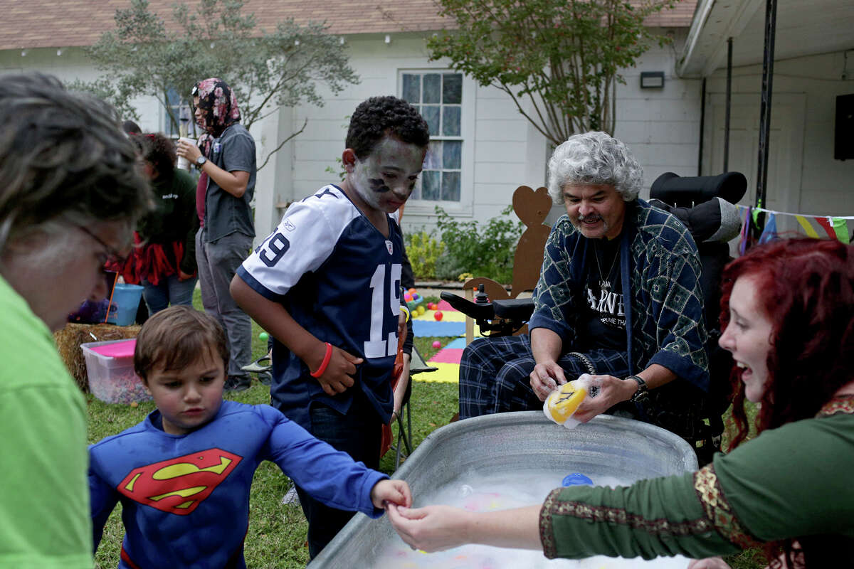 Michelle Shields and her grandson, Michael Kelley, left, play a game run by Gunny Macias, center, and Morgan Workman, right, during Fall Fest at First Baptist Church of Sutherland Springs on Oct. 31, 2018.